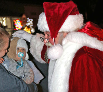 Santa Claus greets 13-month-old Bradford Simms during Christmas in the Park on Wednesday.