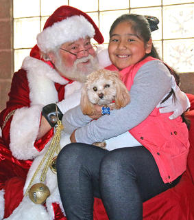 Yuette Carmona and her dog Luna stop for a photo with Santa Claus during Christmas in the Park on Wednesday.