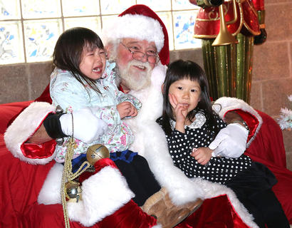 Runa Teshigawara (left) is not happy to meet Santa Claus with her sister Haru Teshigawara (right) during Christmas in the Park on Wednesday.