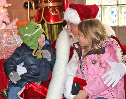Siblings R.J. Sims (left) and Marleigh Sims (right) tell Santa Claus their Christmas wishes during Christmas in the Park on Wednesday.