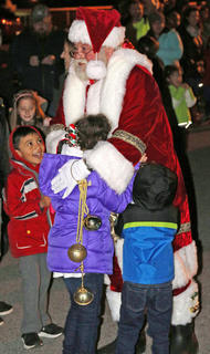 Santa Claus greets a crowd of children as he arrives at Graham Memorial Park for Christmas in the Park on Wednesday.