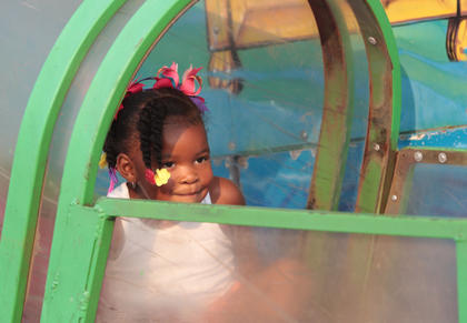 Shamiya Calhoun, 3, of Lebanon peeks over the wall at the end of the Raiders exhibit.