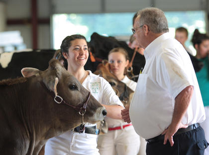 Rachel Hinton of Campbellsville laughs as judge Larry Yager inspects her cow.