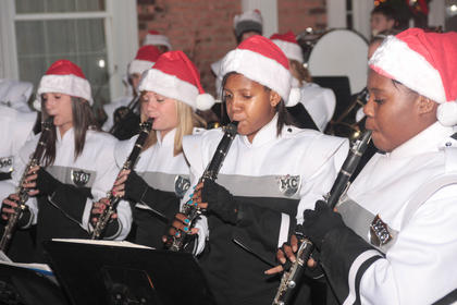 From left, Andrea Ackerman, Kristina Leake, Caitlin Moran, and Labriette Owens perform seasonal music with the Marion County Marching Knights outside Farmers National Bank.