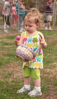 Olivia Spalding, 18 months, takes a moment to examine an egg before placing it in her basket.