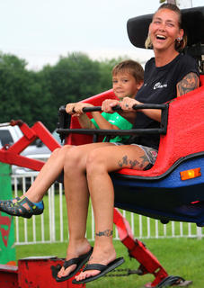 """Carrie Longfellow laughs as her son Phoenix yells, """"I don't want to die!"""" as the ride goes in the air."""