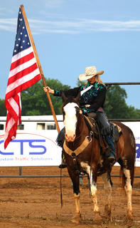 Cowgirl Megan Ery bows her head and proudly holds our nation's flag high during the night's opening invocation.