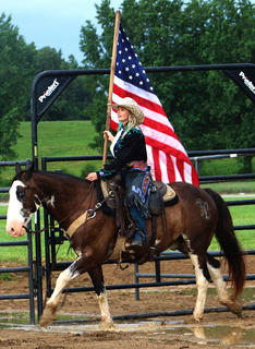 Megan Ery trots around on her horse with the American Flag.