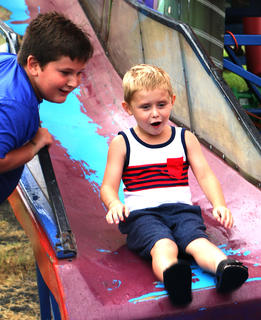 Kaiden Bryant waits at the bottom of the slide as Easton Grinned comes down.