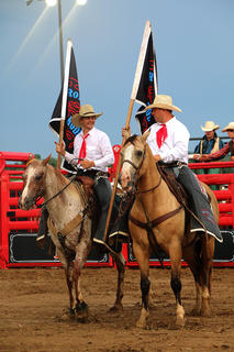 From left, Arthur Antonides and John Stahlan enter the arena to begin the rodeo.