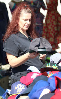 Susan Coulter observes the hat selections at the Ham Days flea market on Saturday.