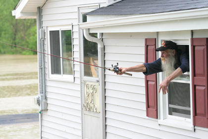 Jimmy Netherland goes fishing from a window in his Calvary home during the flooding that affected Marion County May 2. The floods created problems throughout the county, including flooding the Lebanon Water Works pump station in Calvary.