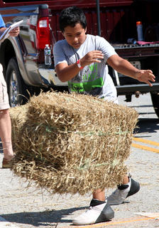 Teegan McCauley tosses a hay bale during the hay bale toss competition on Sunday at Ham Days.
