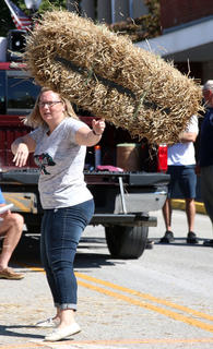 Terry Gabhart of Mackville, Kentucky watches her hay bale in the air during the hay bale toss competition on Sunday at Ham Days.