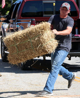 Levi Haydon prepares to toss a hay bale in the hay bale toss competition on Sunday at Ham Days.