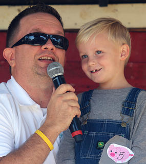 "Sawyer May competes in the Junior Farmer competition at the Marion County Country Ham Days Festival on Saturday morning. Also pictured is emcee Jeremy ""Breakfast Boy"" Bowman."