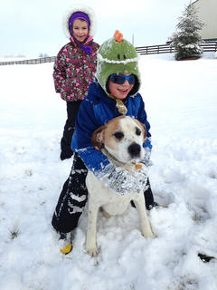 Addison and Braxton Lee play in the snow with their family dog, Cody.