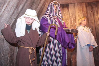 Hunter Delk (shepherd) smiles for the camera as Jeff Delk (one of the wise man) and Beverly Clerk (an angel) gather around the manger.