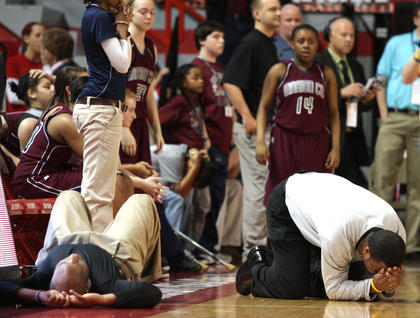 Marion County Lady Knights assistant coaches Anthony Epps and Robert Spalding hit the ground after a heartbreaking loss to Manual.