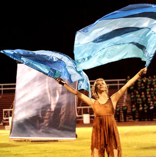 """Christine Cox waves blue flags symbolizing water during the Marion County High School band's show """"Exodus"""" on Saturday in the Marion County Marching Knights Festival."""
