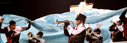 """Cody Abell plays the trumpet as Ethan Rice unveils a blue sheet symbolizing water during the Marion County High School band's show """"Exodus"""" on Saturday in the Marion County Marching Knights Festival."""