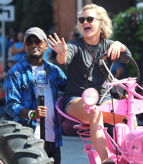 Olivia Carrico waves to the crowd as she drives a pretty pink tractor during the Pigasus Parade. Riding the tractor with her is Trell Cooper.
