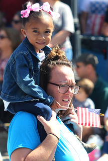 Amber Giles carries ZaRiah Porter on her shoulders during the Pigasus Parade on Saturday afternoon.