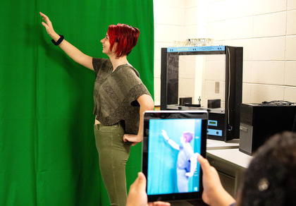 Samantha Bragg is picking an imaginary apple that will come to life with the use of a green screen.