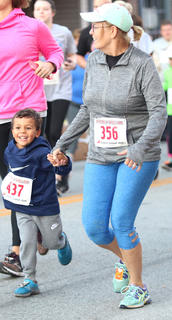 Myles Lawrence, left, and Tonia Greenwell race hand-in-hand at the Pokey Pig on Saturday at Ham Days.