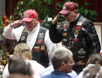 Members of the Patriot Guard Riders salute Deputy Anthony Rakes family after making a small presentation to them.