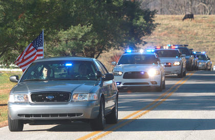 A stream of police and emergency vehicles escorted Rakes from the high school to the Old Liberty Cemetery.