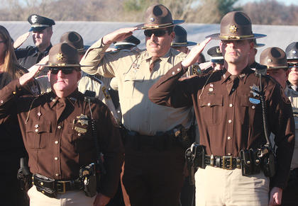 Law enforcement officers salute in honor of Deputy Anthony Rakes.