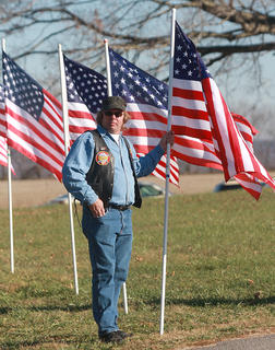 A member of the Patriot Guard Riders holds up one of the many flag placed at the Old Liberty Cemetery prior to the arrival of Deputy Anthony Rakes.