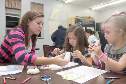 Mary Helen Hamilton, left, helps Brooklyn Deverne and Lillian Mullins with a craft project.