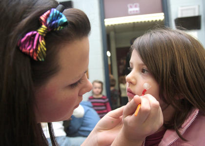 Amber Blandford paints a rainbow on Natalie Wheatley's cheek.