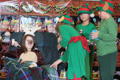 An under-the-weather Rudolph (Jasmine Benningfield) doesn't seem convinced by the medical advice she is being offered by Santa elves, (Sarah Followell, Aleli Huerta and Edson Martinez).