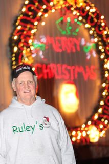 Paul Ruley said he has been decorating his farm for 40 years, and they add more every year. He is pictured in front of the newest addition to his Christmas light display - a 51-foot circumference wreath with 10,000 lights. It took Ruley and a few other men more than eight weeks to build.
