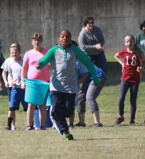 Javon Adams from GES runs down the course as Cheyenne Brown (on right), Alex Wheeler (in pink) and Harry VanWhy (in white) watch his progress.