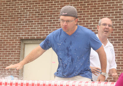 Jeremy Bowman slams down his water bottle to mark his victory in one of the heats in the ham biscuit eating contest.