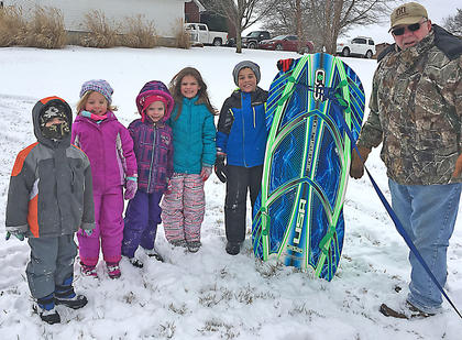 Pictured, from left, are cousins Bo Hutchins, Claire Hutchins, Kylie Hutchins, Adi Hutchins, Connor Hutchins and their grandfather David Hutchins. They all had fun sledding in the snow last week.