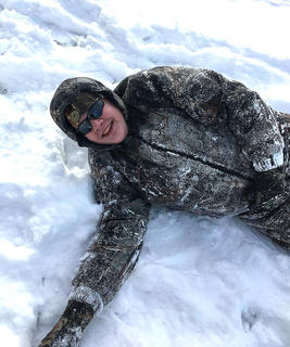 Trevor Mudd lays down in the snow.