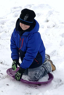 Kaysen Jaeger, 9, of Lebanon goes sledding in Raywick.
