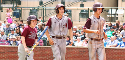 Batboy Sy Bramblett accompaniesDalton Hammond and Kelly Mattingly back to the dugout after they scored on Russell's hit.