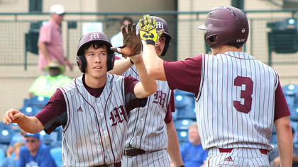 Dalton Hammond is congratulated by No. 3 Landon Russell after scoring on a wild pitch.