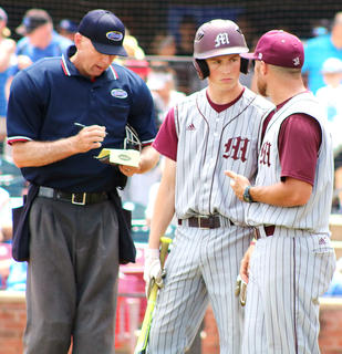 Head Coach Patrick Campbell confers with pinch-hitter Brandon Lee as umpire Todd Saxey writes down the change.