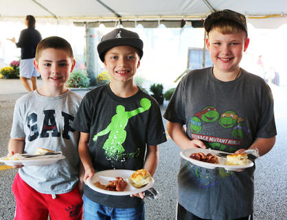 Noah Semones, Landon Wathan, and Blake Wathan show off their breakfast plates.