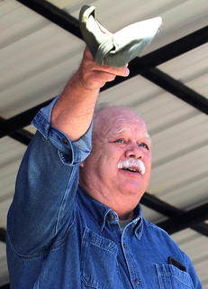 Terry Currens bows to the crowd after competing in the hog calling contest at the Marion County Country Ham Days Festival on Saturday afternoon. He was named the overall male winner.