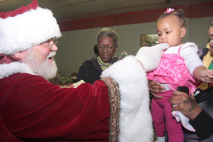 Santa tickles the chin of Ky'laya Keene, 10 months.