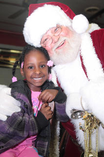 Kyra Cowherd, 4, poses for a photo with Santa at the toy giveaway Dec. 22 at the Cardinal Den.