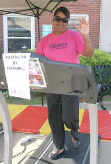 Kim Bell waves during her turn on the treadmill.